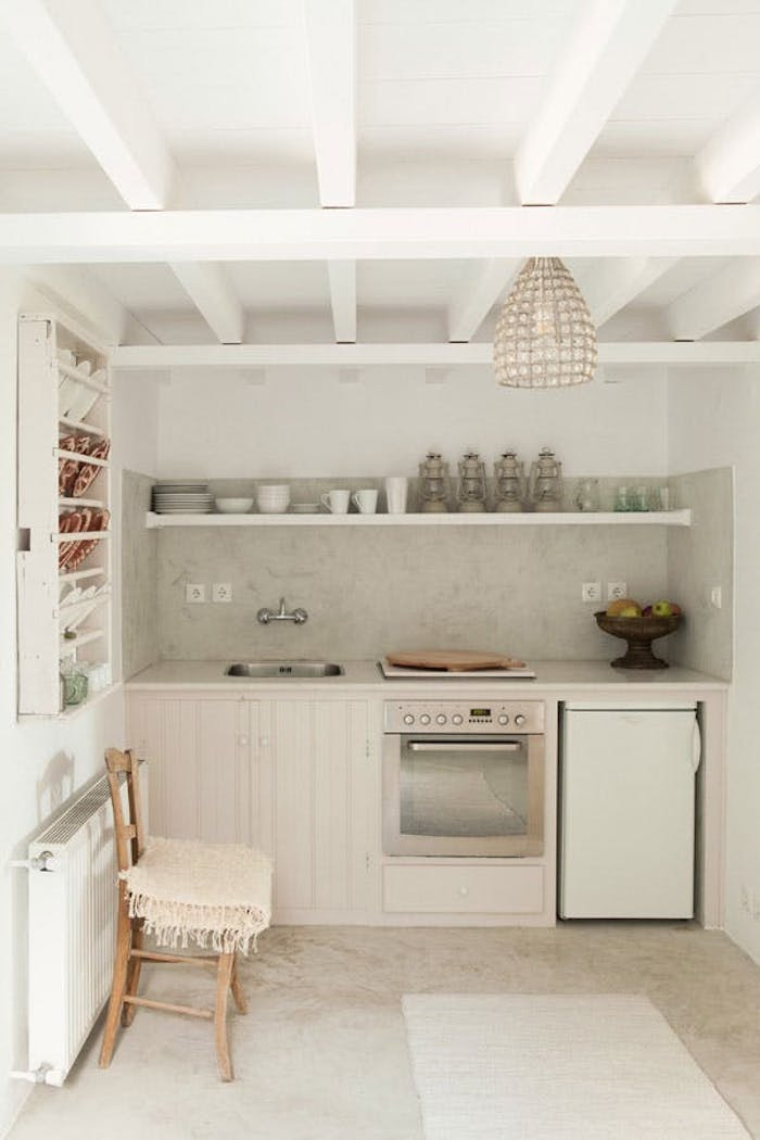 minimalist kitchen in white and ivory, with small fridge, modern stove and several cabinets, retro sink and chair, decorative plates and gas lanterns