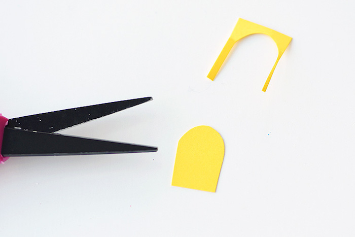 easter projects, scissor blades in black, near a small yellow paper cutout, white background