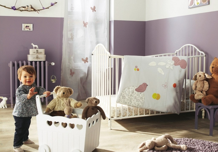 lavender and white walls, in a baby's room, with white metal crib, girl nursery themes, smiling toddler pushing white cart with toys