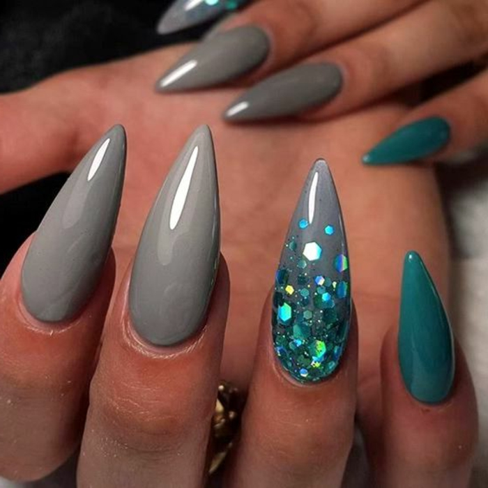 acrylic manicure covered with smooth, grey and turquoise nail polish, long and sharp stiletto nails, with iridescent light blue glitter