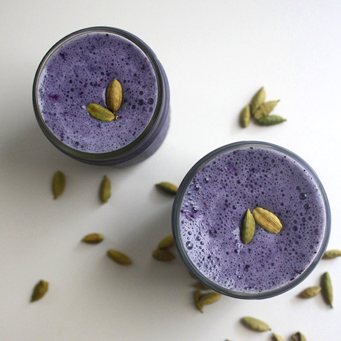 seeds topping two glasses, filled with frothy purple smoothie, protein shake recipes, more loose seeds nearby