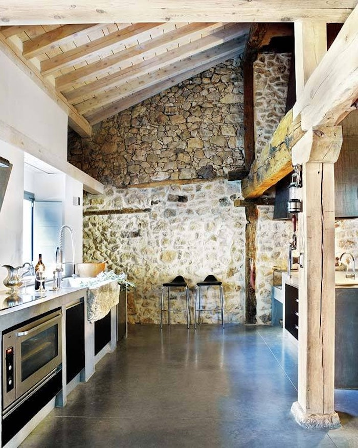 high vaulted ceiling, enforced with wooden planks and beams, inside a large kitchen, with dark smooth floor, modern appliances and stone-covered wall