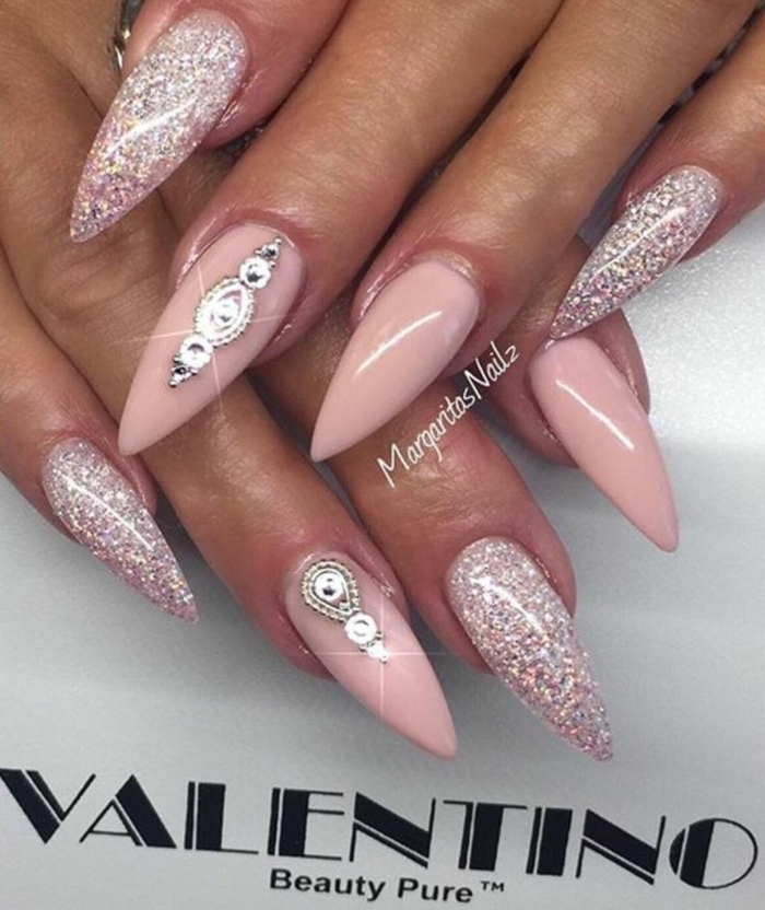 valentino long stiletto nails, with pink and silver glitter, and pastel pink nail polish, decorated with silver stickers