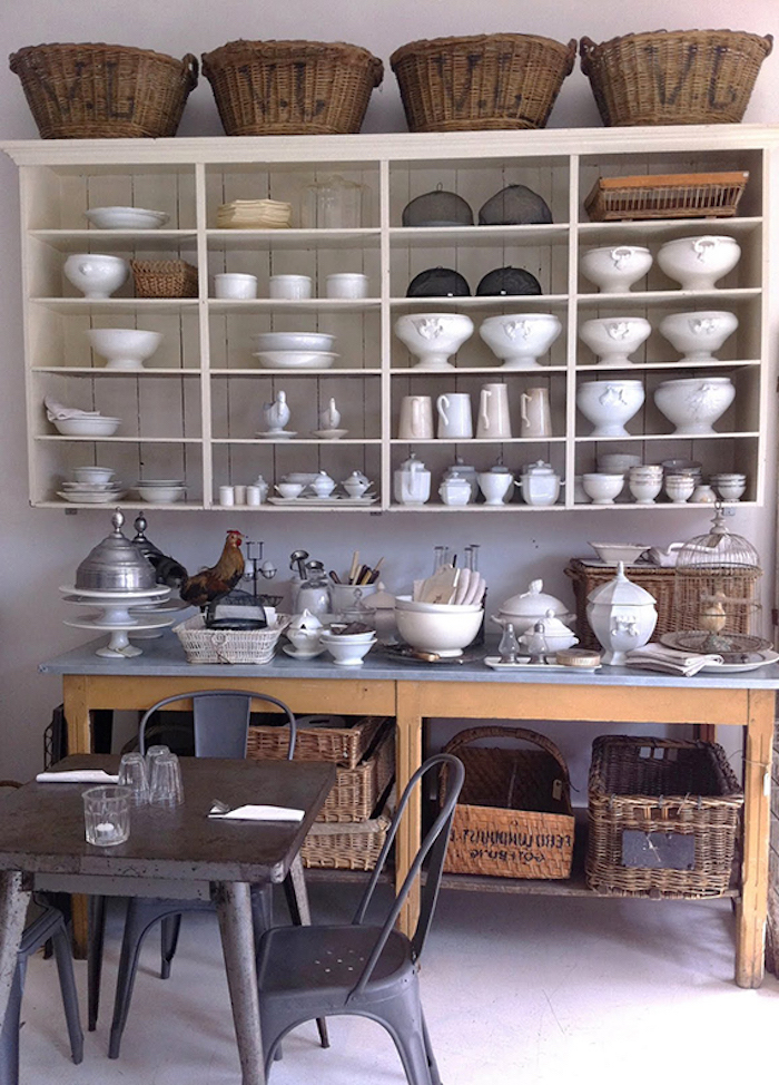 soup dishes and mugs, bowls and jugs, inside an off-white cupboard, near large wooden counter, covered with various dishes and crockery, and a small square black metal table, with matching chairs