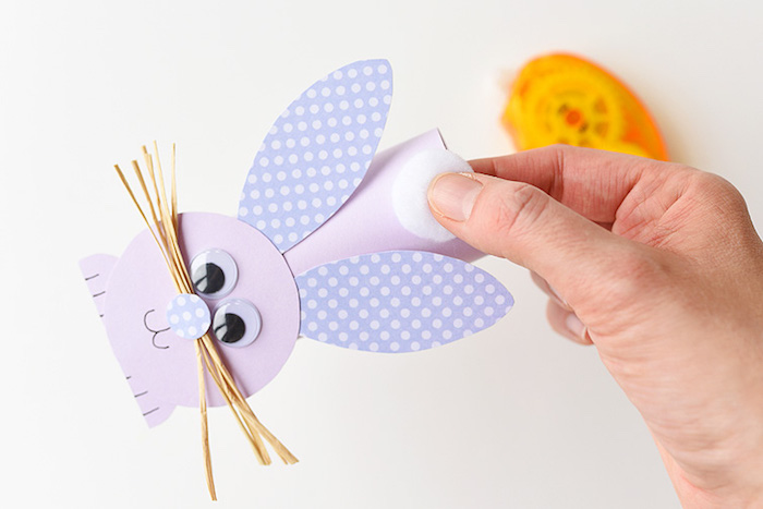 attaching a white cotton ball tail, to bunny figure, made out of pale purple card, easter diy, cute festive idea