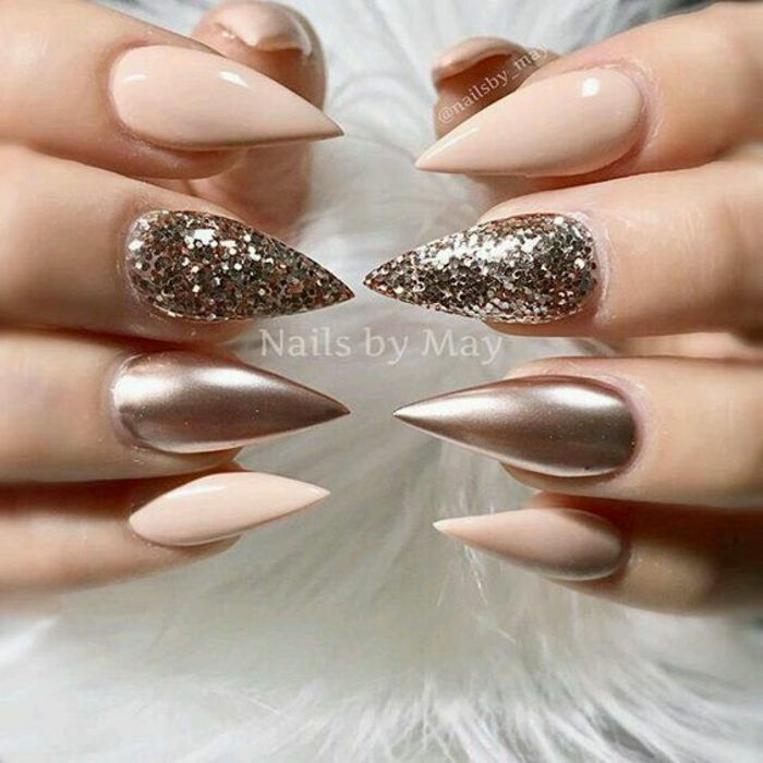 very sharp and pointed, pale pink nails, decorated with rose gold metallic effect, and sparkly glitter