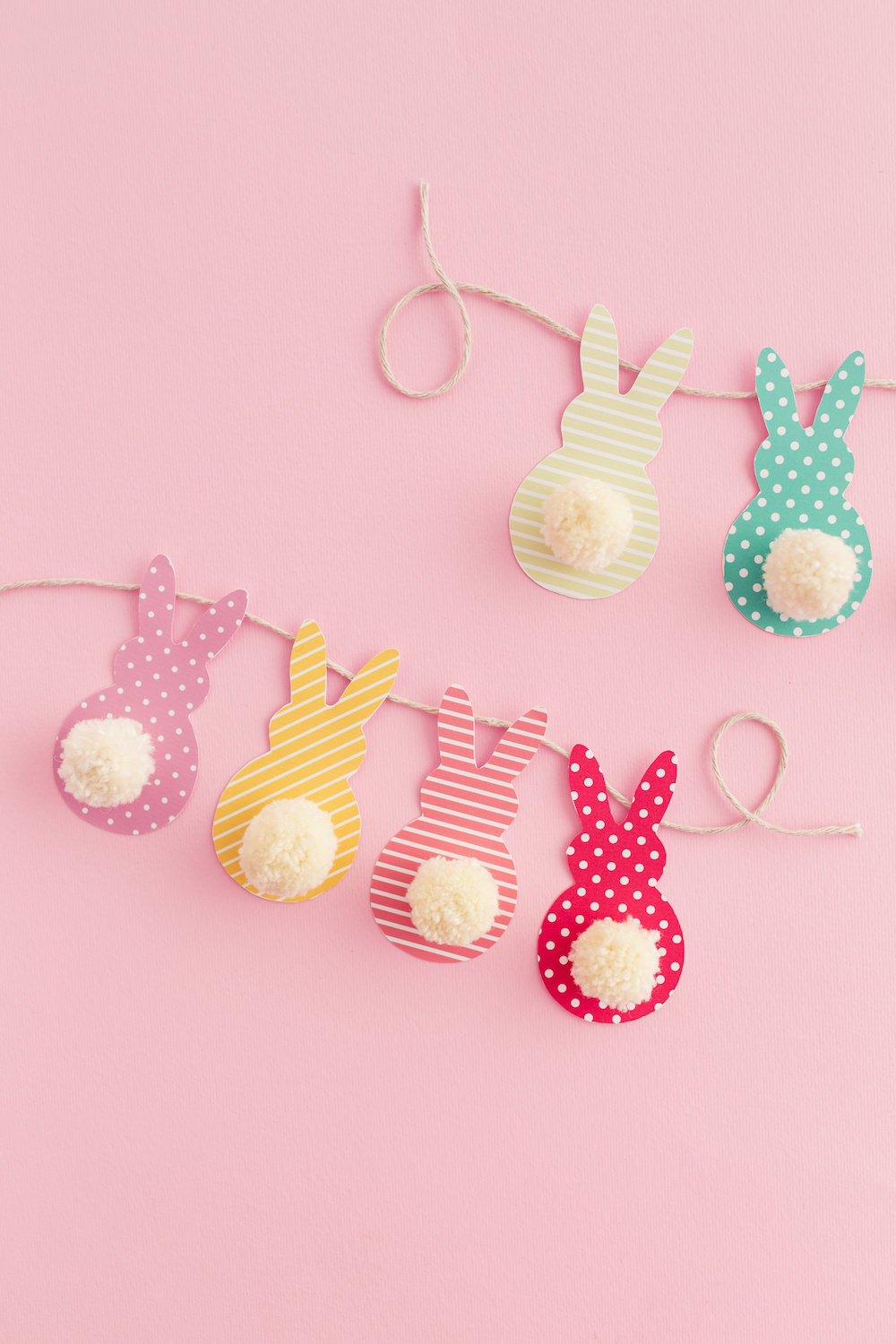 easter crafts for kids, garland made from string, and colorful patterned paper, cut in rabbit shapes, with little white cotton ball tails