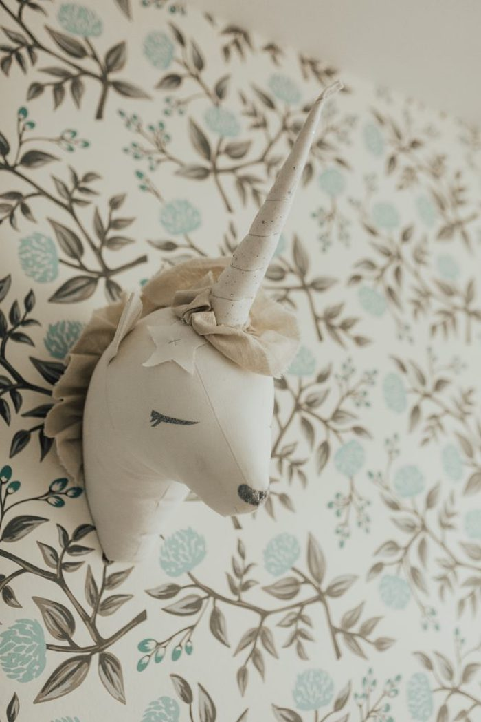 unicorn head made of fabric, mounted on a wall, baby girl nursery ideas, with white wallpaper, featuring a pale blue, and olive green floral pattern