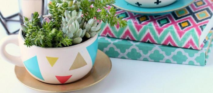 coffee cup decorated with colorful triangles, placed over a golden saucer, containing dirt and several planted succulents, good mothers day gifts, multicolored books in background