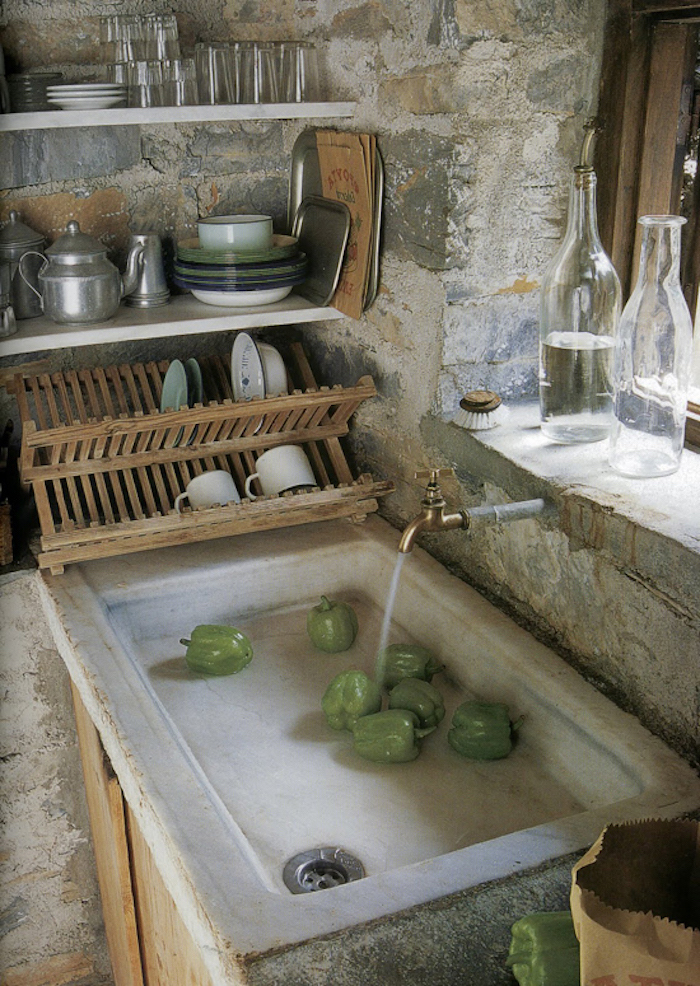 natural stone sink basin, containing seven green peppers, vintage tap with running water, country kitchen décor, stone covered walls, simple white shelves, and a wooden dish drying rack