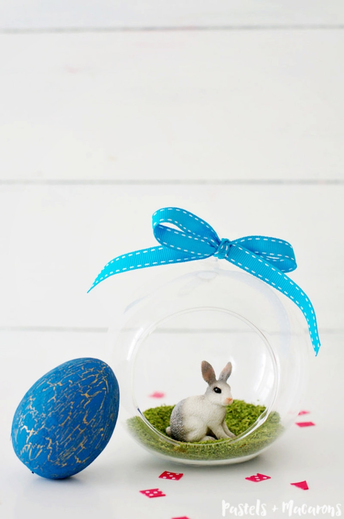 round glass container with opening, tied with a blue bow, containing a layer of green moss, and a realistic rabbit figurine, easter projects, dyed easter egg in blue and gold nearby