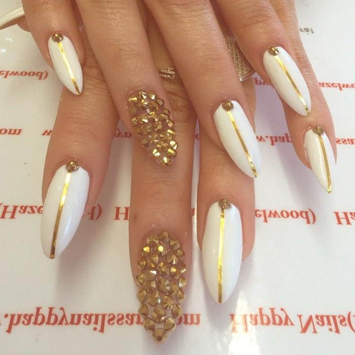 encrusted nails with gold rhinestone stickers, white nail polish, decorated with thin golden stripes, long oval and sharp manicure