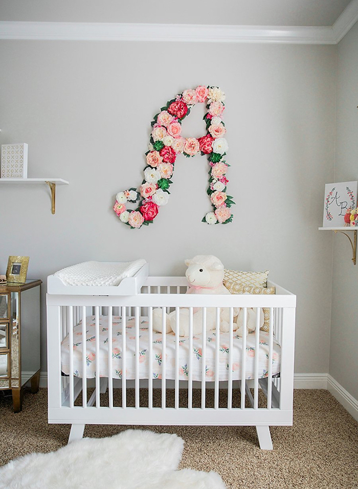 floral arrangement with white, light and dark pink faux roses, forming the latter a, over a white wooden crib, baby girl themes, floral bedding and stuffed sheep toy