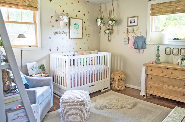 chest of drawers, made from massive pale brown wood, near white crib, baby girl nursery ideas, three hanging potted plants, plush ram's head decoration