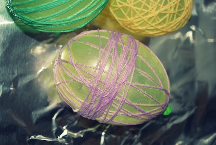 several small pale green balloons, wrapped in purple, green and yellow thread, easter arts and crafts, placed on a sheet of tin foil
