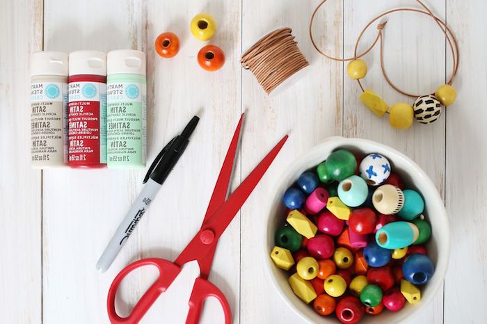 scissors in red, white bowl filled with multicolored wooden beads, mothers day gifts, three tubs of paint, thread and a pen