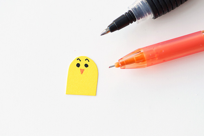 drawing a bird's face, with orange and black pen, drawing a face, on small yellow cutout