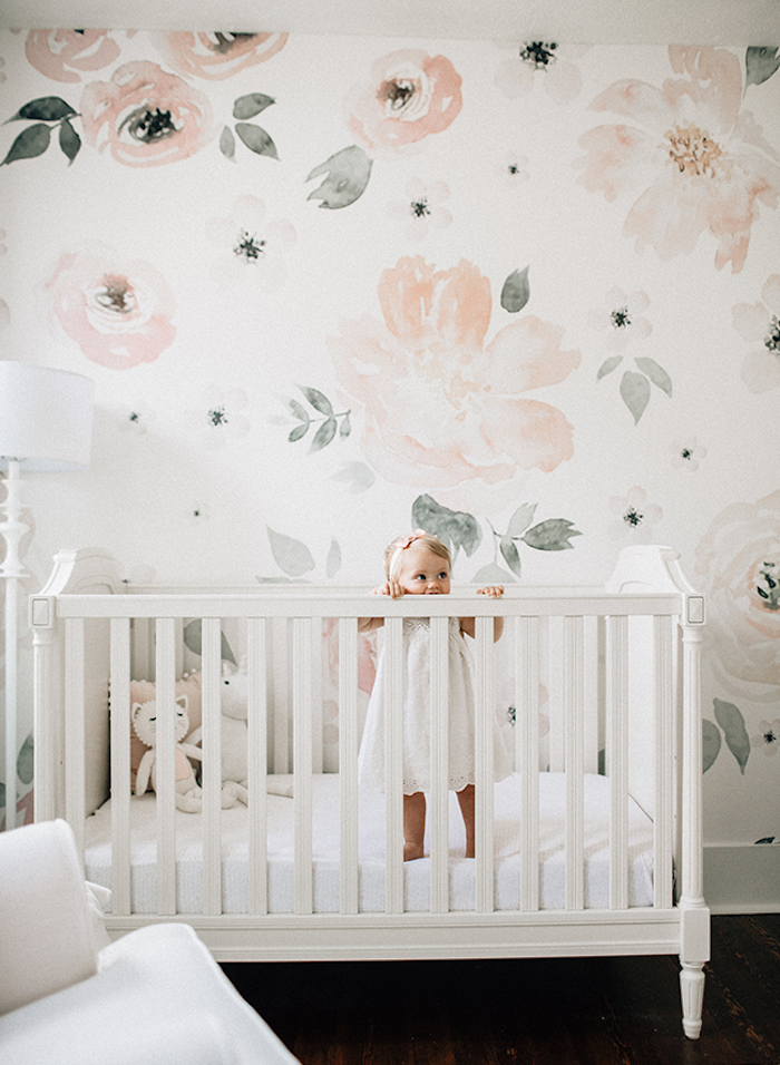 little toddler girl, standing in white, ornate wooden crib, baby girl themes, near white wall, with pale pastel, water color-like floral print