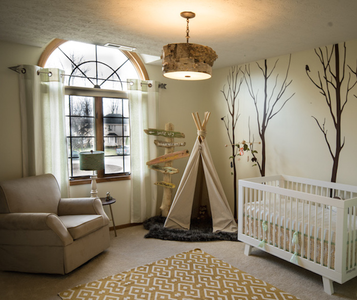realistic wall mural, with three dark brown trees, near tipi or teepee, made from beige fabric and wood, baby nursery ideas, white crib and beige armchair