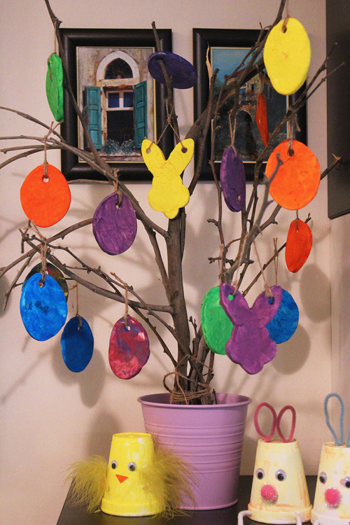 easter tree, made from dried branches, decorated with differently colored, hand-crafted and hand-painted ornaments, shaped like eggs and bunnies, easter crafts for preschoolers, more hand-made decorations nearby