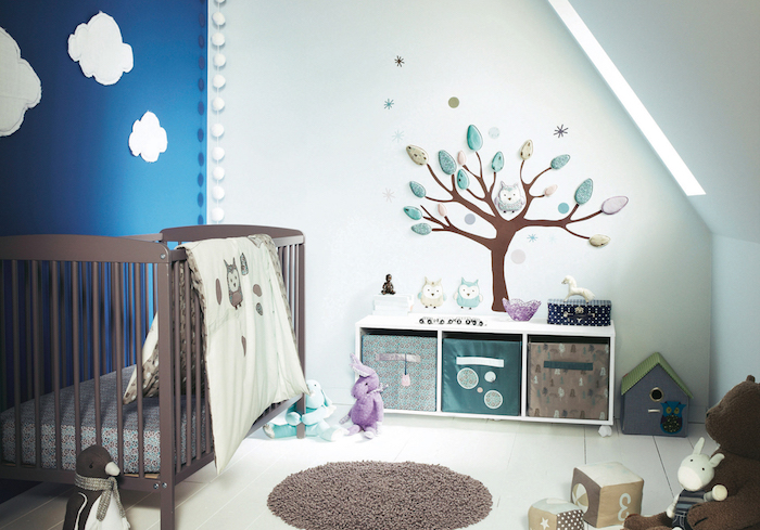 white clouds painted on a blue wall, in boy nursery, other visible wall is white, and features a tree mural, with colorful leaves and owls, brown wooden crib