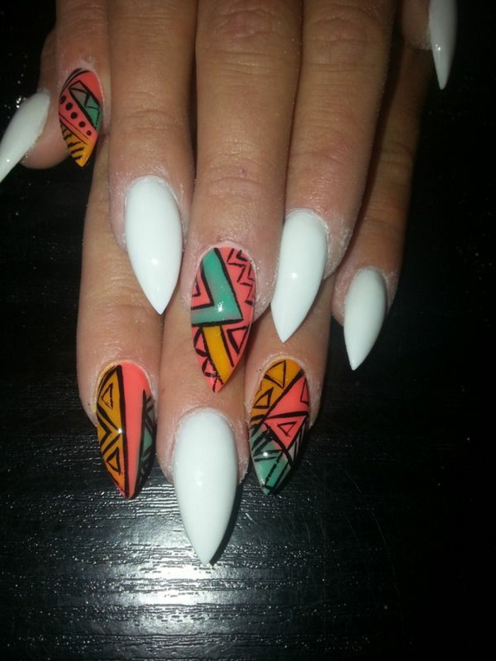 tribal motives in turquoise, yellow and pink, on sharp nails, with opaque white nail polish
