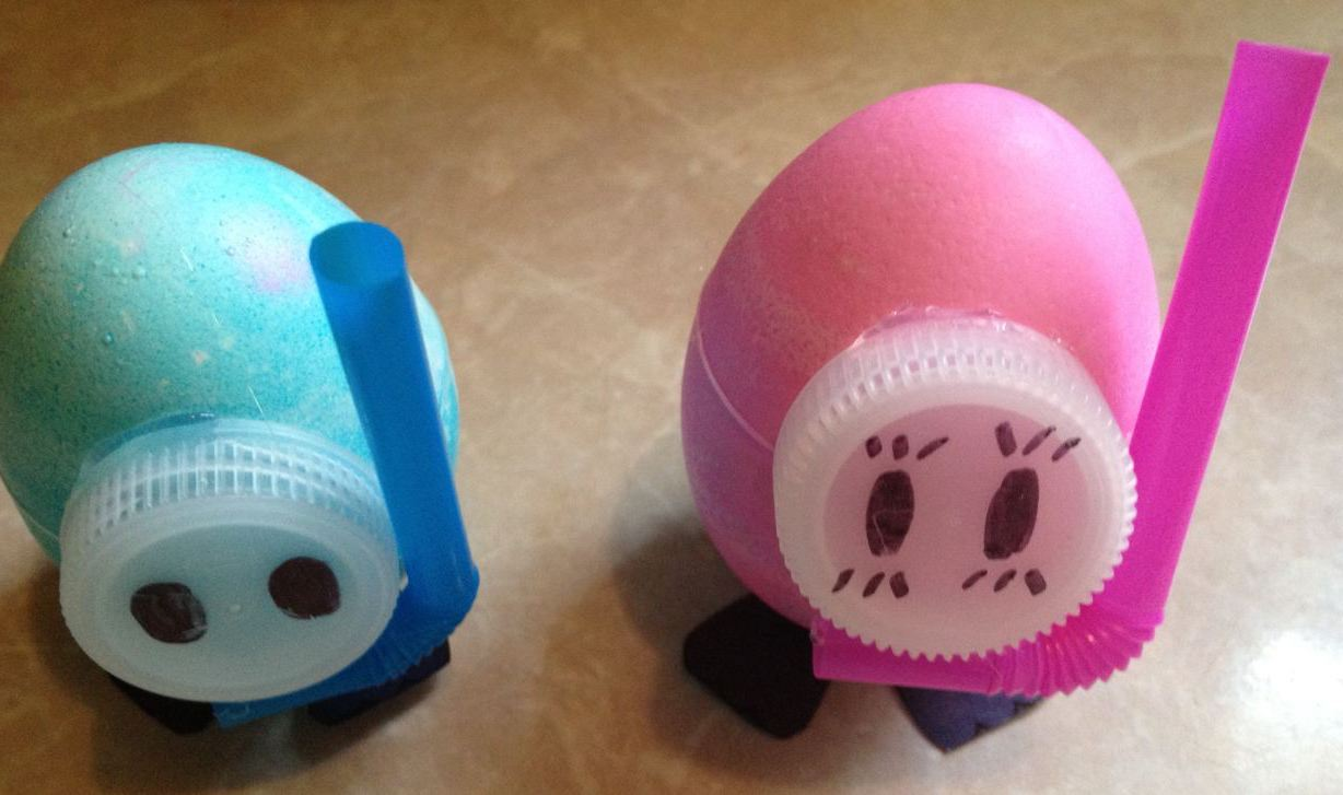 dyed eggs in pale pink, and light turquoise, decorated with sheer, plastic bottle caps, and bendy straws, easter crafts for preschoolers, made to look like snorkeling divers