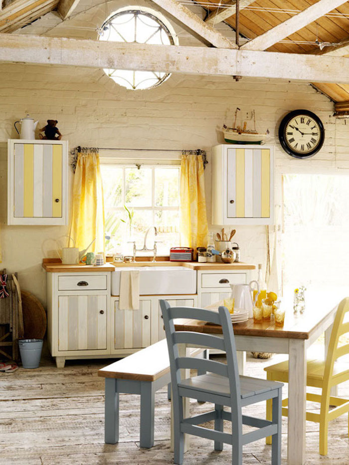 chairs in pastel blue and yellow, near small square wooden table and bench, inside a room with white brick walls, ceiling beams and wooden floor, pale grey and white, striped country kitchen cabinets