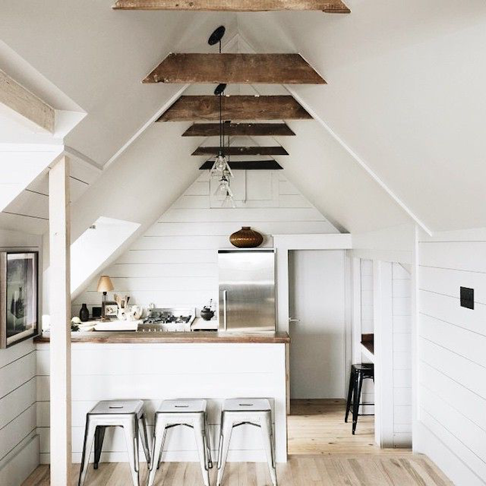 three shabby chic stools, near a kitchen counter, inside a room with light laminate floor, metal fridge and white vaulted ceiling, with brown beams