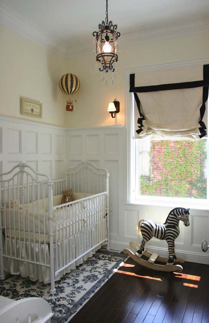 boys room ideas, vintage inspired nursery, dark wooden floor, white rug with blue floral baroque pattern, ornate white baby crib, antique black lamp