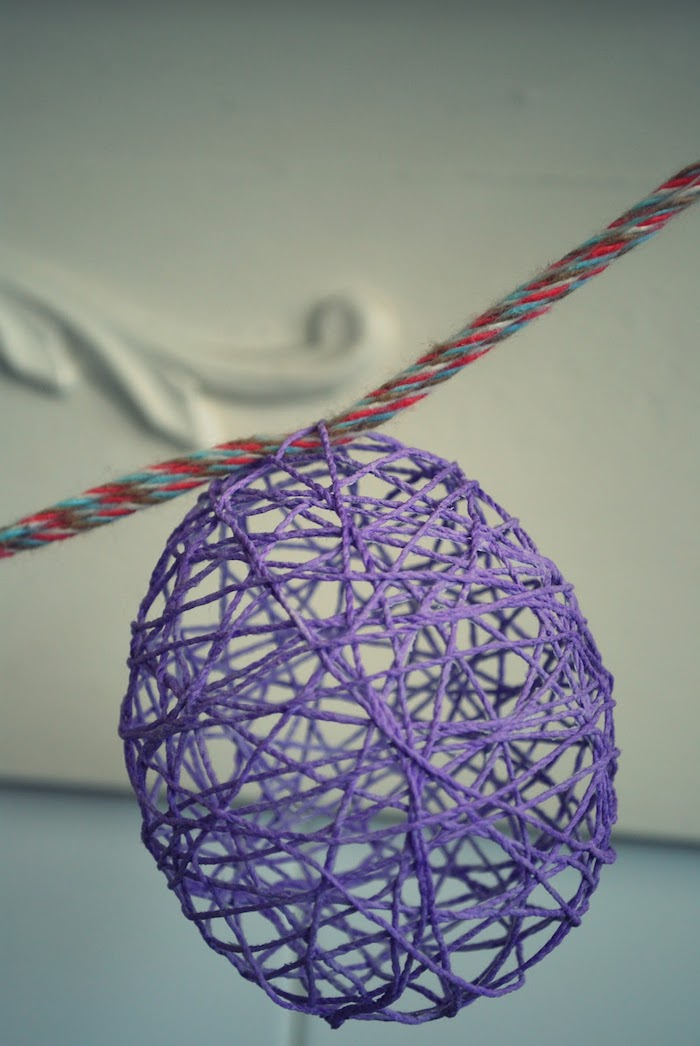 close up of a purple, meshy and hollow egg-shaped ornament, easter arts and crafts, hanging on multicolored woven rope