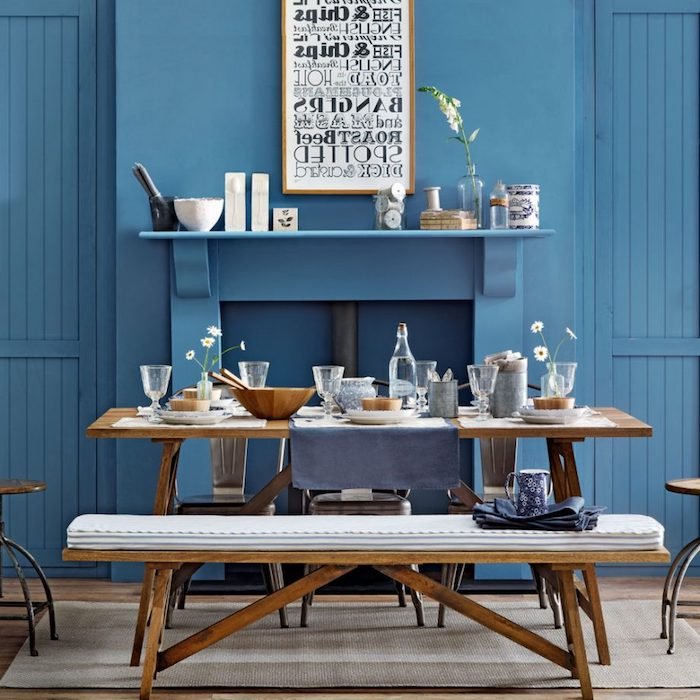 vivid blue walls, and a fireplace, inside a dining room, with light brown wooden table, matching bench and chairs, country kitchen décor, bowls and plates, mugs and glasses