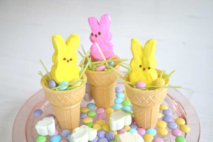 peeps shaped like bunnies, in yellow and pink, placed in light wafer cones, with green easter glass and candy, on plate with marshmallows, and other sweets