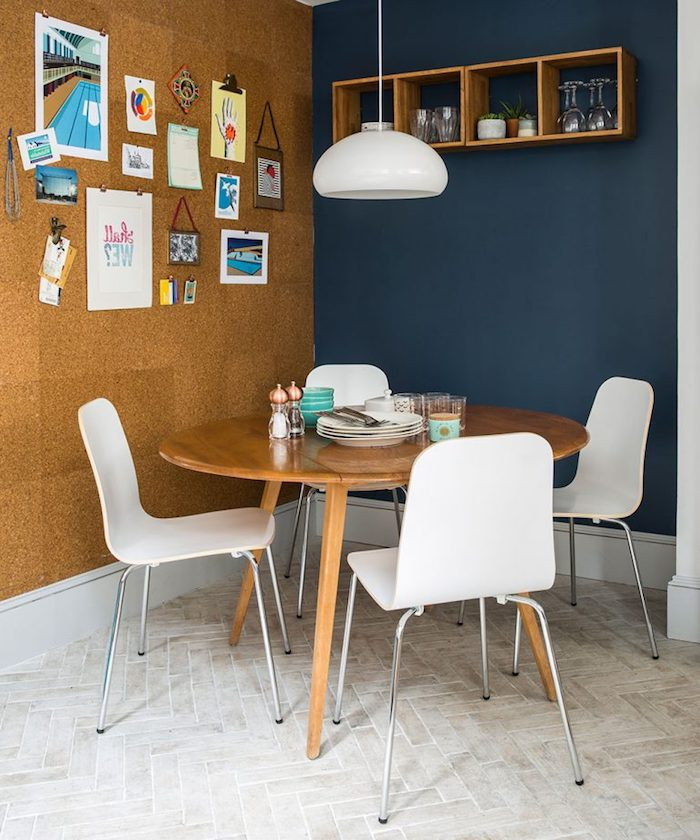 contrasting walls in navy and beige, one with four square wooden shelves, the other decorated with various photos, images and drawings, country kitchen décor, round wooden table, with four modern white chairs