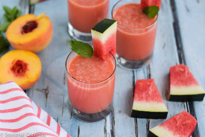 peach cut in two, near three glasses, filled with a blended watermelon drink, easy smoothie recipes, decorated with watermelon slices