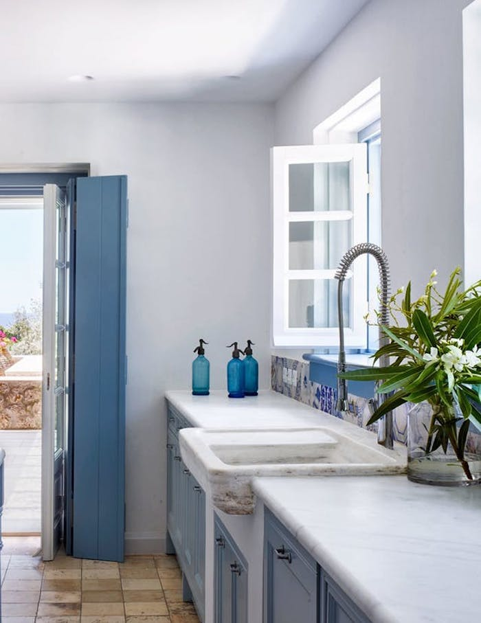 pale blue rustic kitchen cabinets, inside white room, with stone sink, and modern metal water tap, opened window and door, floor with beige stone tiles