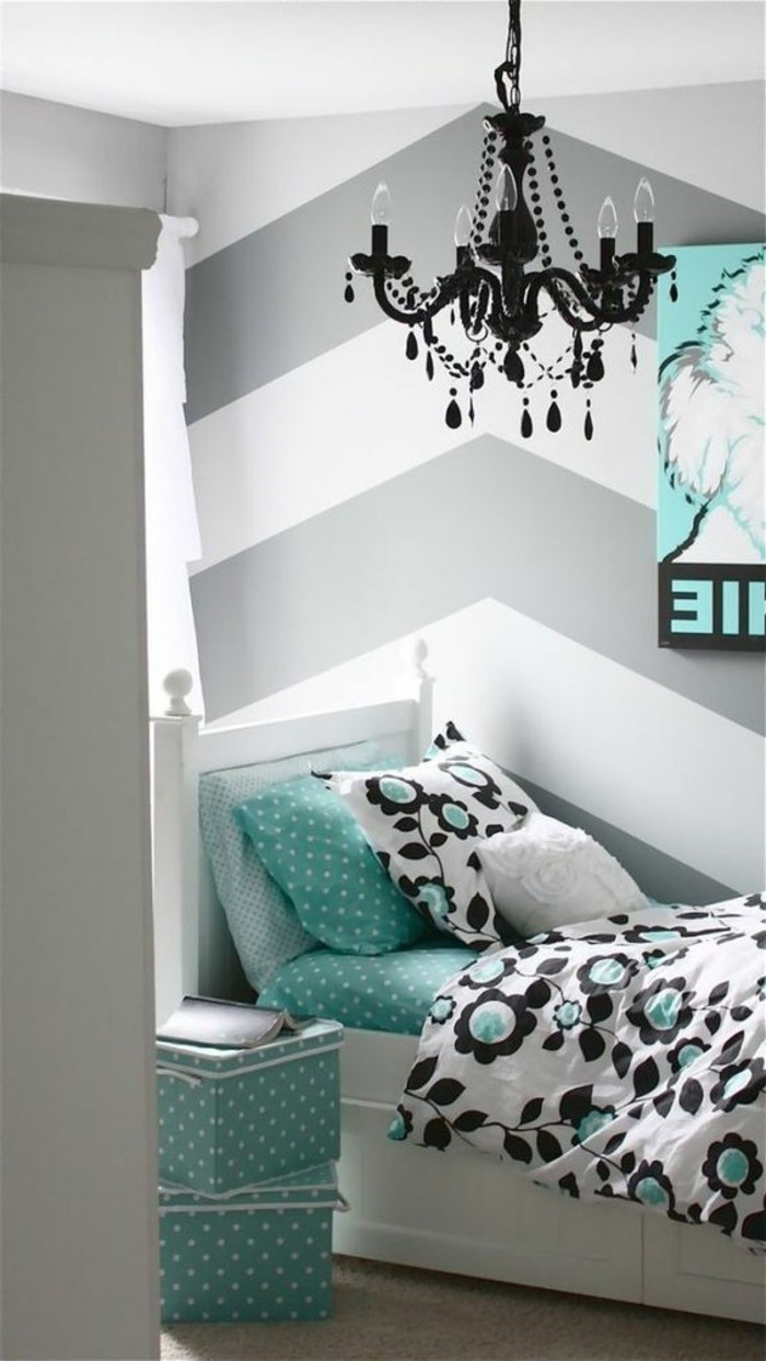 floral motives in black and teal, on white bed with teal bedding and pillow, striped walls in white and grey bedroom, ornate black baroque-style chandelier