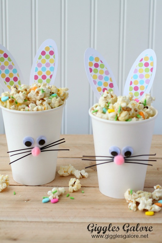 cups made from white paper, decorated with rabbit ears, googly eye stickers, pom pom noses, and black fuzzy wire whiskers, containing multicolored popcorn, great easter idea