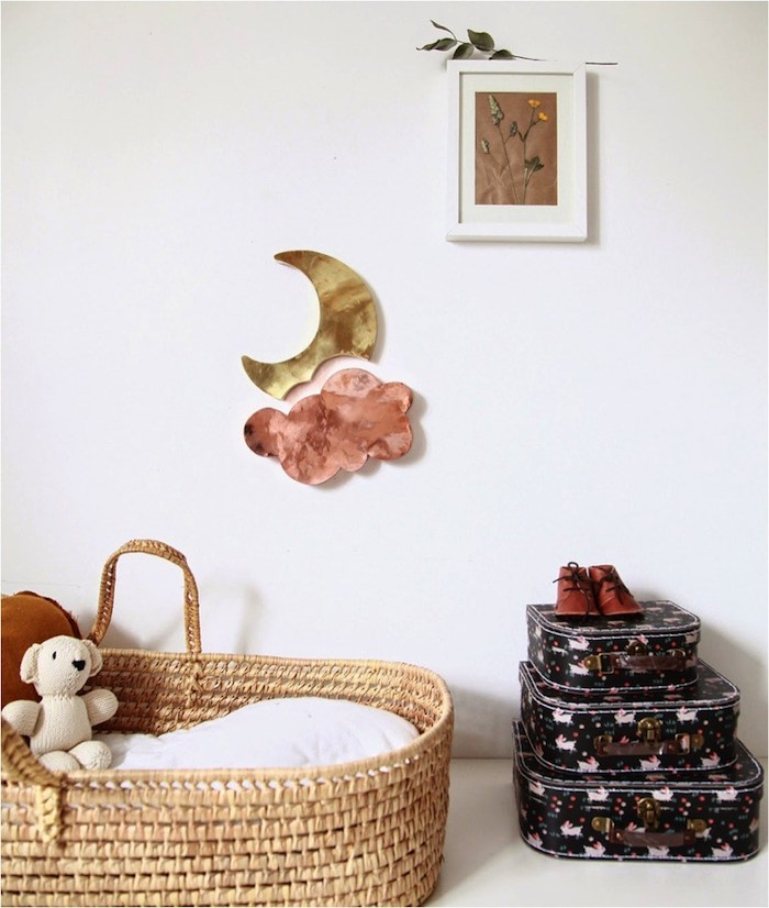moon and pink cloud wall decoration, near wicker baby basket, three small decorative suitcases, framed dried flowers, baby girl nursery ideas