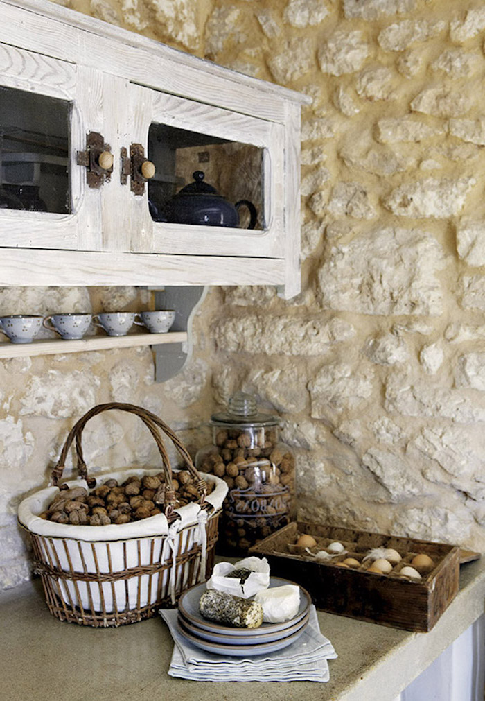walnuts inside a basket and a large jar, near wooden box filled with eggs, and several gray plates, sandy-yellow stone wall, pale gray rustic cupboard