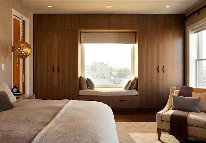 space-saving closet, wardrobes and matching cupboards, made of wood, surrounding a window, beige bed and armchair, window seat with cushions