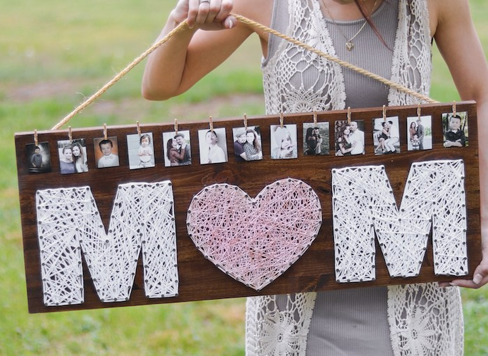 large board made of wood, decorated with photos, and the word mom, written in large letters, using thread and nails, top 10 mother's day gift ideas, rope handle held by slim woman