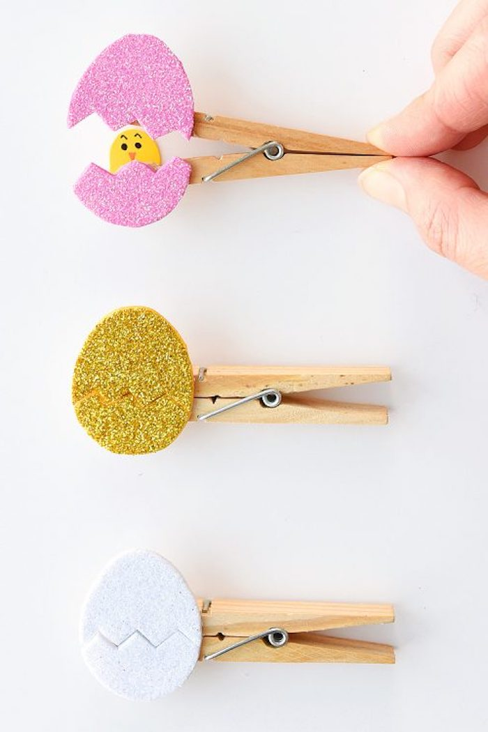 hatching egg ornaments, containing yellow paper chicks, easter arts and crafts, made with glittering card, in different colors, and wooden clothespins