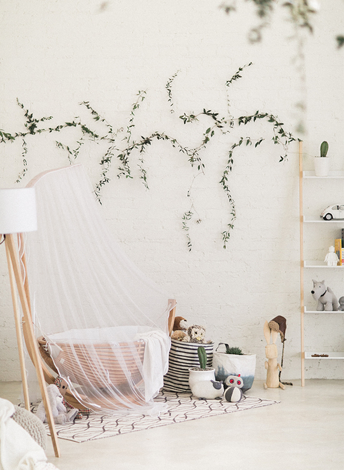 organic nature-inspired, gender neutral nursery, with white walls, wooden baby basket, with sheer white baldachin, various green plants and toys