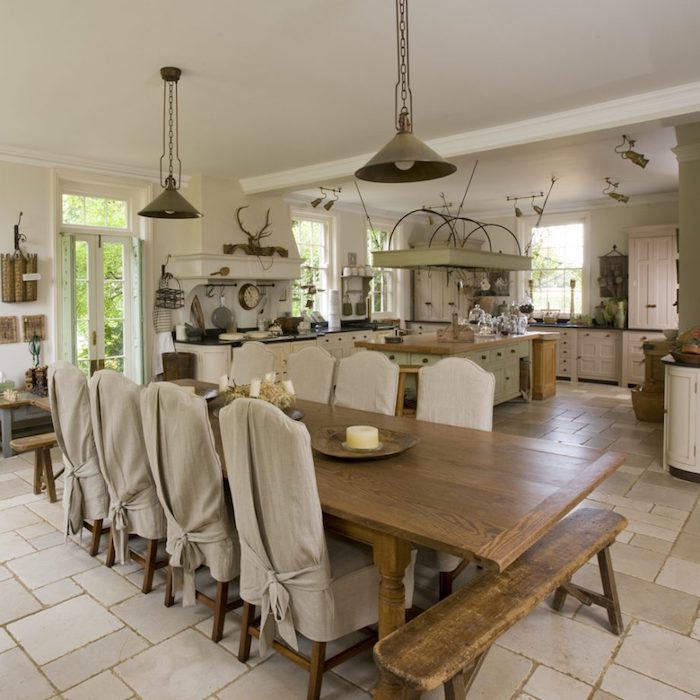 spacious kitchen with large dining table, worn wooden bench, and four chairs covered in beige cloth, rustic country home décor, white cupboards and appliances, various decorative objects