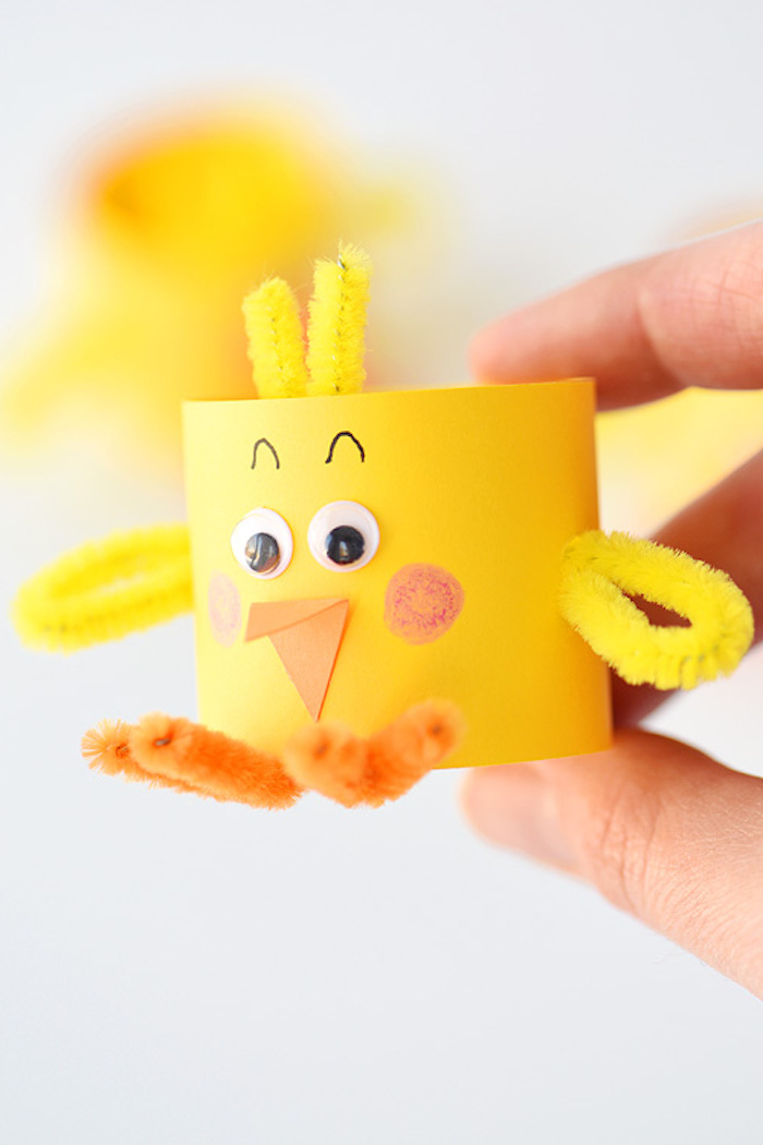 fuzzy wire in yellow and orange, stuck to small, yellow paper tube, decorated to look like a chick, held in a person's hand