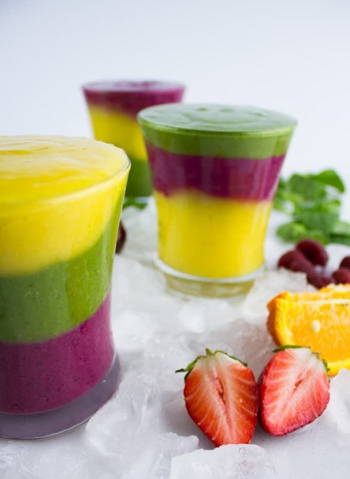 layered blended fruit drinks, purple yellow and green smoothie, in three glasses, near pieces of strawberry, orange and mint