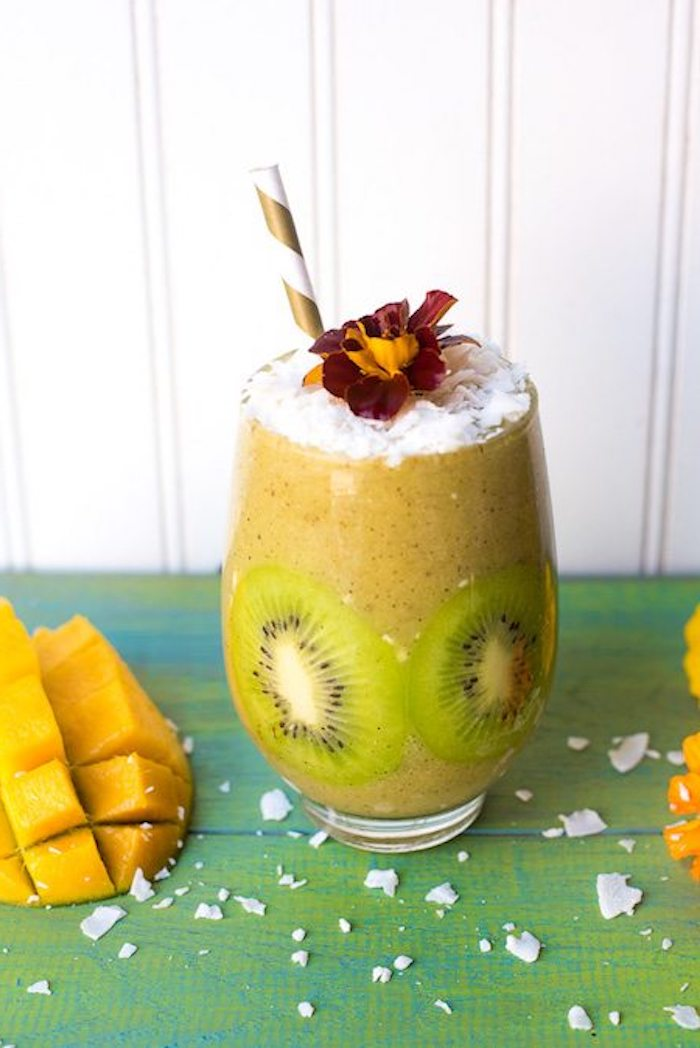 mango and kiwi blended drink, decorated with kiwi slices, easy smoothie recipes, topped with coconut flakes, and a red and yellow flower