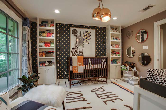 spacious room with large framed zebra painting, on dark gray wall, with white and yellow dots, brown wooden crib, baby nursery ideas, shelves and mirrors
