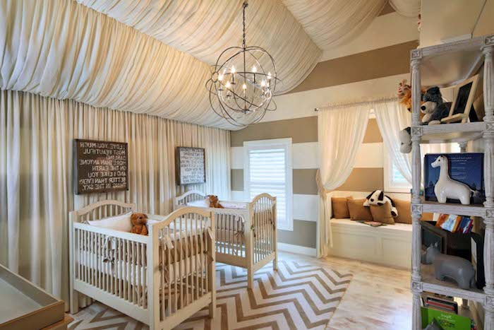 set of two cribs, in white and pale beige, each containing a teddy bear, baby nursery for twins, zig zag beige and cream carpet, white curtains and vintage shelf